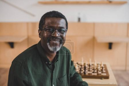 smiling mature man with chess