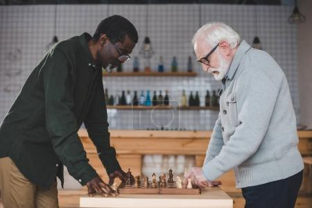 Photo for Side view of concentrated senior men playing chess in bar - Royalty Free Image