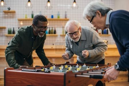 Photo for Group of senior friends playing table football at bar - Royalty Free Image
