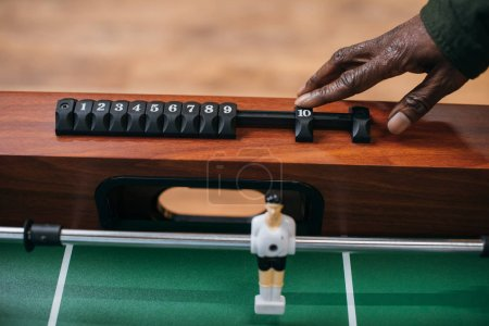 man moving counter on table football