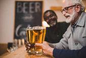 senior friends clinking beer glasses