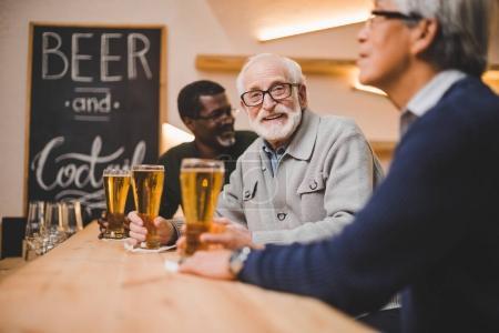 senior friends drinking beer together