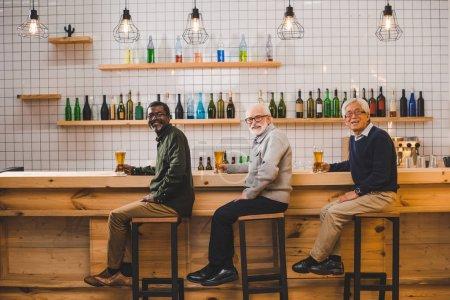 Photo pour Groupe d'amis aînés buvant de la bière ensemble - image libre de droit