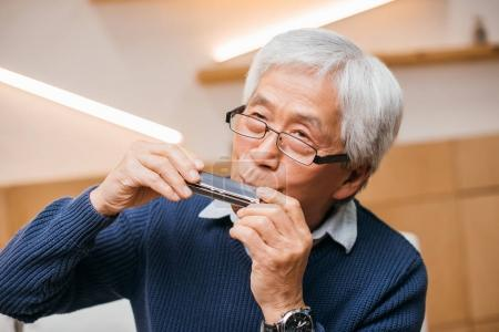 Photo for Portrait of happy senior asian man playing harmonica - Royalty Free Image