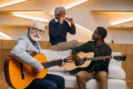 Photo pour Groupe d'amis de hauts beau jouer de la musique avec guitare et harmonica - image libre de droit
