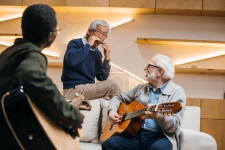 Photo for Group of happy senior friends playing music with guitars and harmonica - Royalty Free Image