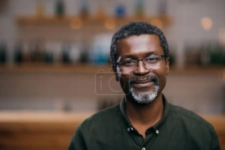 Photo for Happy african american mature man in front of blurred bar counter - Royalty Free Image