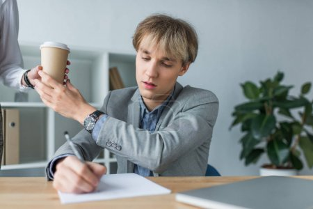 woman giving coffee to colleague
