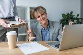Homme d'affaires surpris assis à l'ordinateur portable