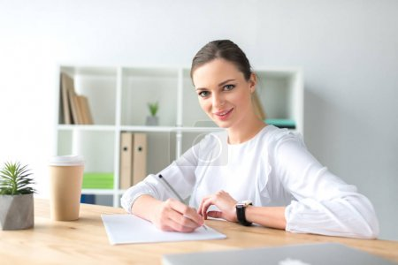 happy businesswoman sitting at table
