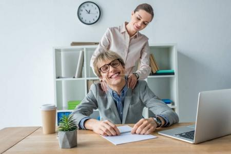 Photo for Businesswoman massaging shoulders to colleague at office - Royalty Free Image