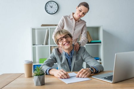 woman massaging shoulders to colleague