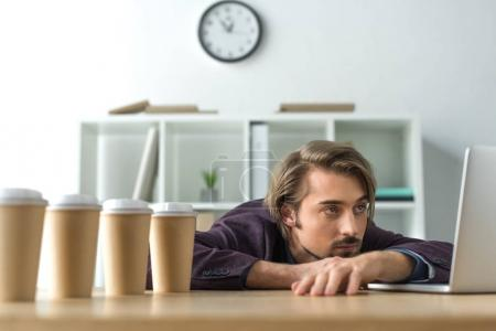 Tired businessman lying on table