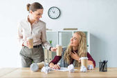 Woman bringing coffee to colleague