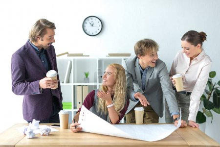 Photo for Four colleagues talking and drinking coffee while working at the office - Royalty Free Image
