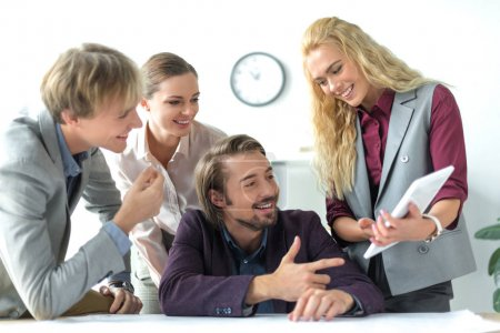 Photo for Smiling business partners looking at tablet - Royalty Free Image
