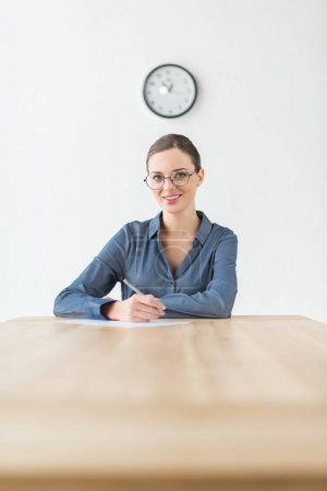 Photo for Smiling businesswoman sitting at the table and holding pencil in hand - Royalty Free Image