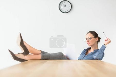 Photo for Businesswoman reading documents and sitting with legs on table - Royalty Free Image