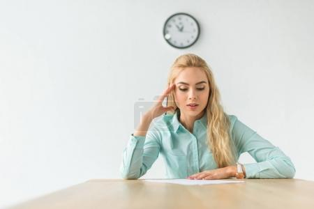 Photo for Businesswoman sitting at the table and looking at documents - Royalty Free Image