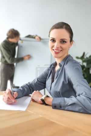 Photo pour Femme d'affaires souriant assis à la table et en regardant la caméra - image libre de droit