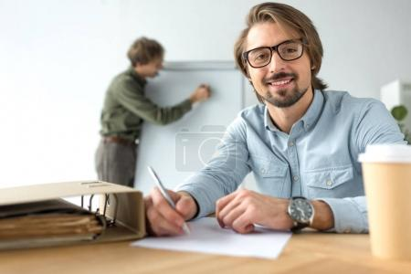 smiling businessman sitting at table