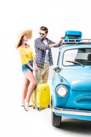 couple putting luggage on car roof