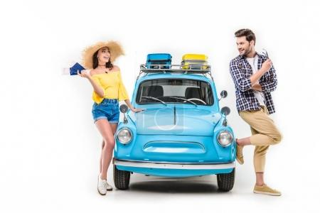 Photo pour Young tourists standing by car and holding flying tickets isolated on white - image libre de droit