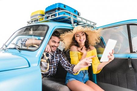 Photo for Young happy couple of travelers sitting in car and looking at map isolated on white - Royalty Free Image