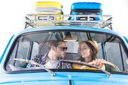 Photo for Young happy couple of tourists driving car and looking at each other isolated on white - Royalty Free Image
