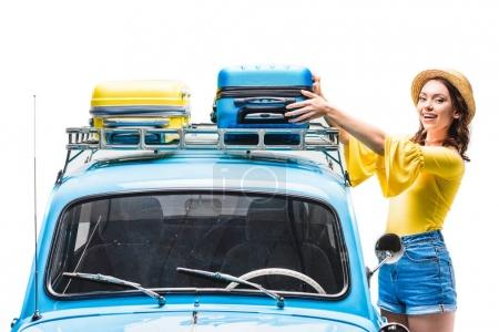 woman putting luggage on car roof
