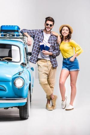 Photo pour Beau jeune couple de voyageurs avec des billets debout à côté de voiture vintage isolé sur blanc - image libre de droit