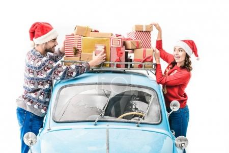 couple with christmas gifts on car roof