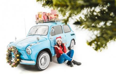 Young woman sitting near car with christmas gifts ...