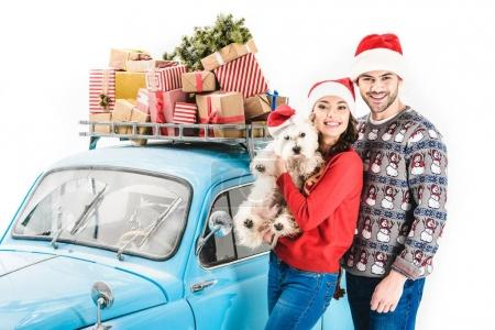 Photo for Young couple with White Terrier and christmas gifts on car roof isolated on white - Royalty Free Image