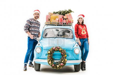 Photo for Young couple with christmas gifts on car roof isolated on white - Royalty Free Image