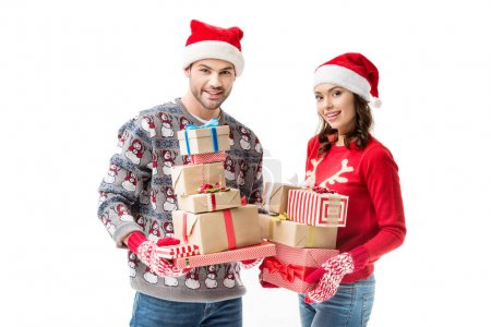 Photo for Happy young couple holding stacks of christmas gifts and looking at camera isolated on white - Royalty Free Image