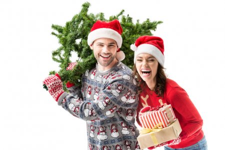 Photo for Happy young couple carrying christmas tree and stack of christmas gifts isolated on white - Royalty Free Image