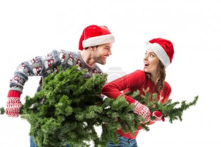 Photo for Excited young couple carrying christmas fir tree together isolated on white - Royalty Free Image