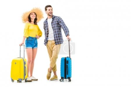 Photo for Attractive couple of tourists holding luggages and looking away isolated on white - Royalty Free Image