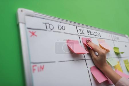 Photo pour Vue recadrée de femme d'affaires mettant note collante sur le tableau des tâches - image libre de droit