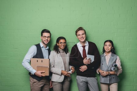 young multiethnic businesspeople with digital devices and documents standing in front of green wall