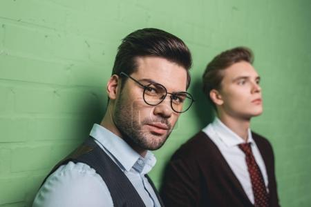 young handsome men in front of green wall