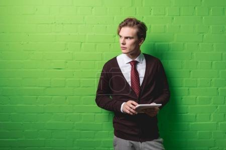 Photo for Young businessman with digital tablet in front of green wall - Royalty Free Image
