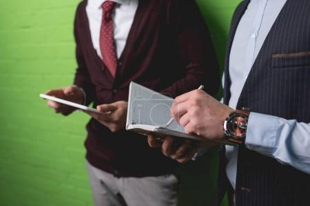 cropped view of businessmen working with digital tablet and notepad in front of green wall