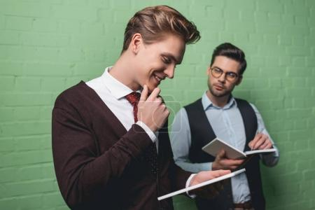 Photo for Young businessmen working with digital tablet and notepad in front of green wall - Royalty Free Image