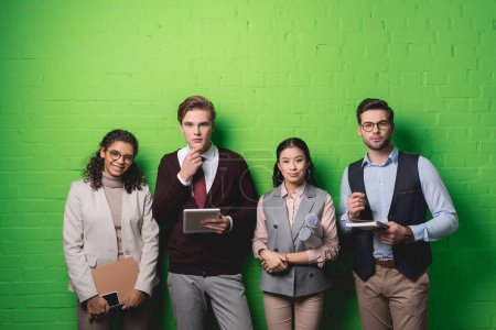 Photo for Young multiethnic businesspeople with digital devices and documents standing in front of green wall - Royalty Free Image
