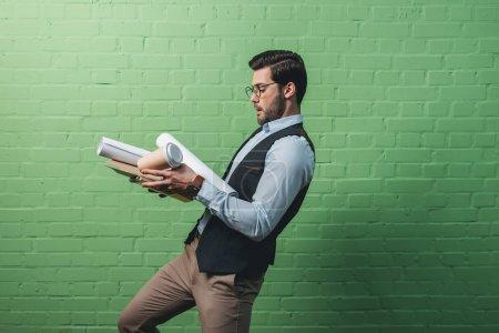Photo pour Homme d'affaires occupé avec tablette, documents et tasse de café devant le mur vert - image libre de droit