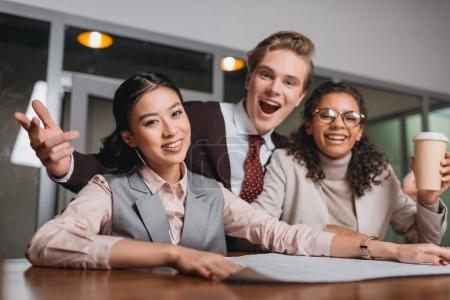 Photo for Excited multicultural businesspeople with coffee and documents working in office - Royalty Free Image