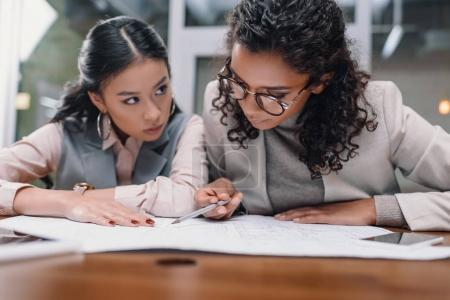 Photo for Concentrated multiethnic businesswomen working with documents in office - Royalty Free Image