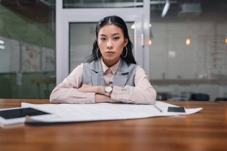 asian businesswoman working with blueprint and digital devices in office